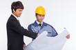 Asian business man and engineer having a blueprint.