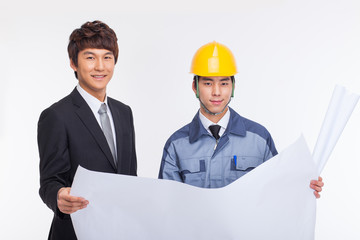 Asian business man and engineer having a blueprint.