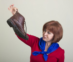 Unhappy woman holding a dirty shoe.
