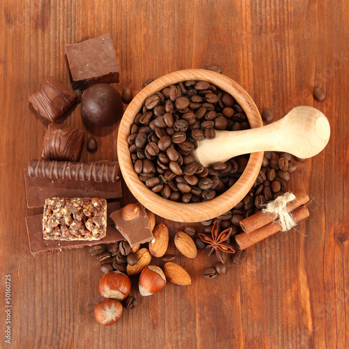 Chocolate sweets, mortar with coffee beans on wooden background