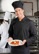 Chef Presenting Dish In Kitchen