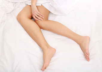 Young woman lies on her bed with long legs