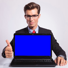 business man with laptop & thumb up