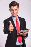 holding tablet & making thumbs up gesture