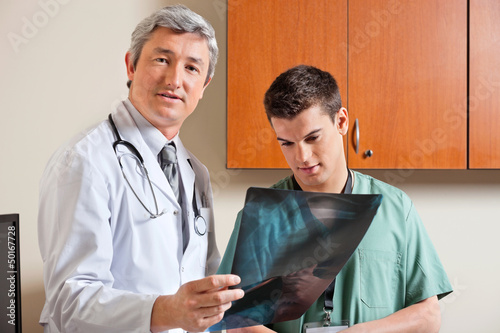 Radiologist Standing With Male Technician