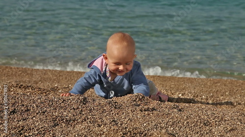 Baby playing and crawling on the beach