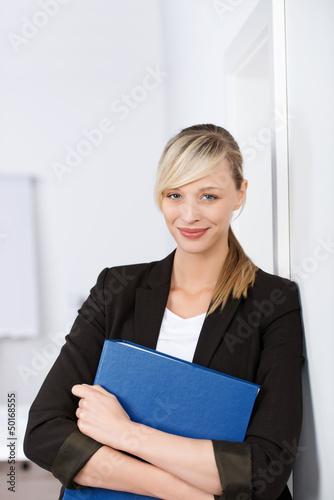 lächelnde geschäftsfrau lehnt an der wand