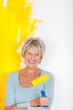 seniorin streicht eine wand gelb