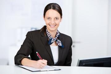 freundliche mitarbeiterin füllt ein formular aus