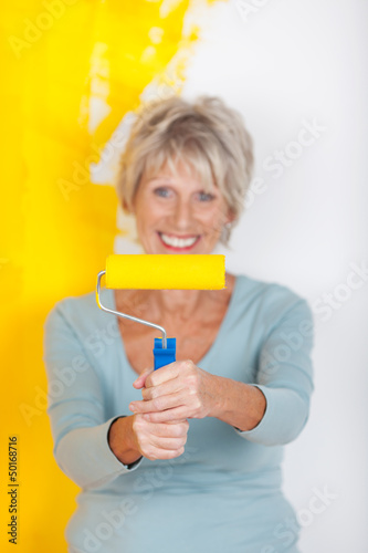 aktive seniorin streicht ihre wohnung