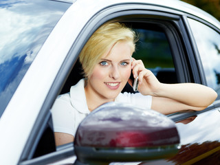 Blond girl sitting in her car has a call with smartphone