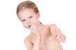 Portrait of child brushing teeth with sign OK and thumb up