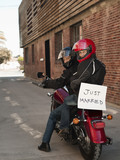 Caucasian couple riding on motorcycle with Just Married sign