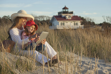 Caucasian mother and daughter using digital tablet on beach