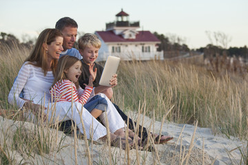 Caucasian family using digital tablet on beach