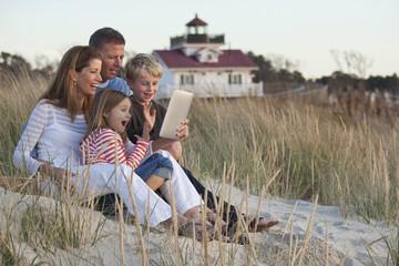 Caucasian family using digital tablet on beach