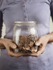 Caucasian woman holding jar of coins
