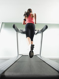 Mixed race woman running on treadmill
