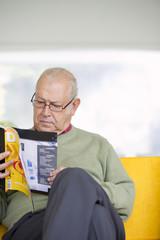 Senior Hispanic man reading magazine