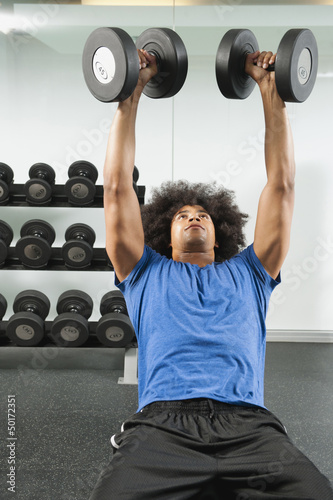 Black man lifting dumbbells in gym