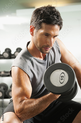 Mixed race man lifting dumbbells in gym