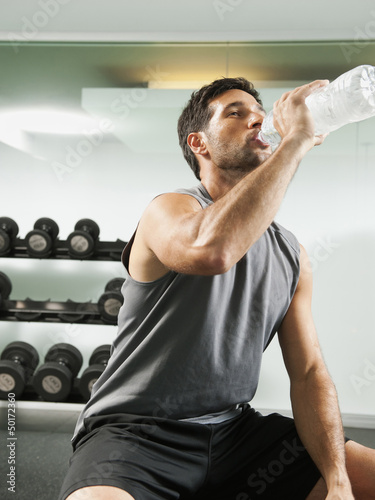 Mixed race man drinking water in gym
