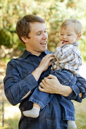 Caucasian father holding son outdoors