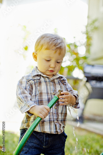 Caucasian boy playing with garden hose