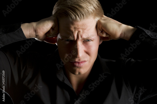 Low key portrait of overburdened young man.