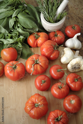 Tomatoes, garlic and basil on cutting board