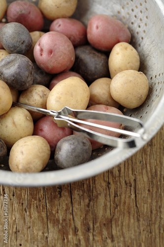 Peeler in colander with multicolored potatoes