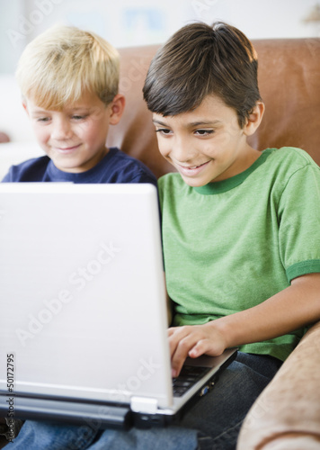 Boys using laptop together