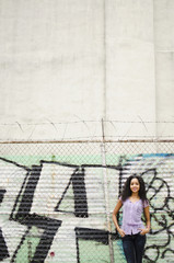 Middle eastern woman standing near graffiti