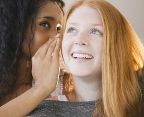 Woman whispering in friend's ear