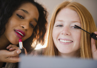 Smiling woman putting on makeup