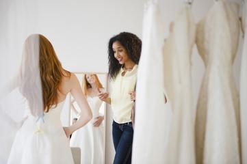 Woman helping friend try on wedding dress