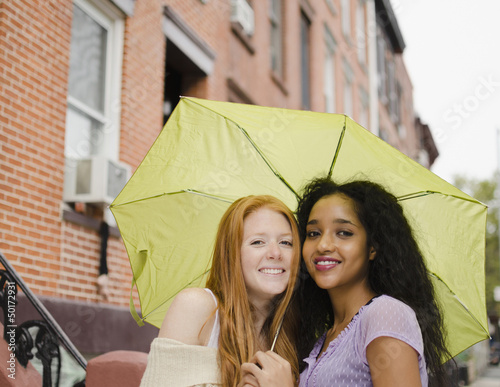 Friends sharing umbrella outdoors