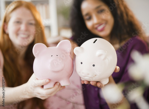 Friends holding piggy banks