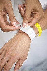 Nurse putting identification bracelet on patient in hospital