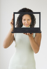 Hispanic woman holding laptop in front of her face