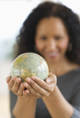 Hispanic woman holding small globe