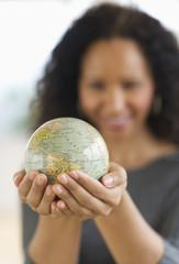 Hispanic woman holding small globe