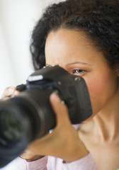 Hispanic woman taking photographs with camera