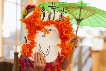 Caucasian girl holding homemade mask