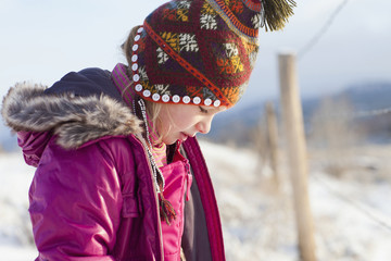 Caucasian girl in cap and coat outdoors