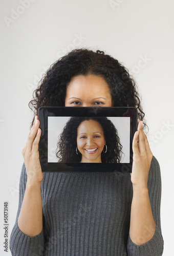 Hispanic woman holding digital tablet in front of face