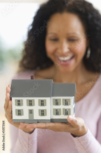 Hispanic woman holding miniature house