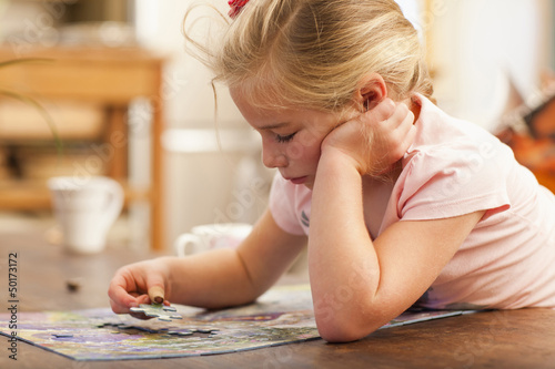 Caucasian girl putting puzzle together