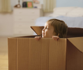 Mixed race boy playing in cardboard box