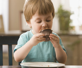 Mixed race boy eating cupcake
